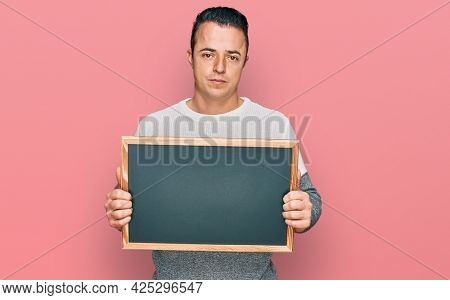 Handsome young man holding blackboard thinking attitude and sober expression looking self confident