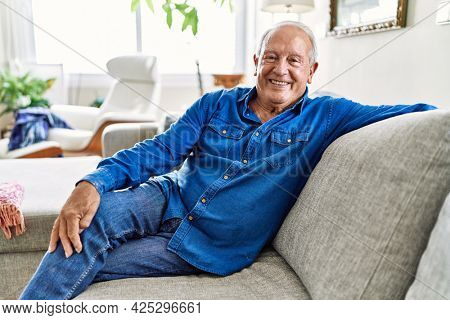 Senior man with grey hair sitting on the sofa at the living room of his house. Mature man smiling happy at home.