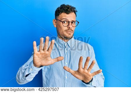 Young hispanic man wearing casual clothes and glasses moving away hands palms showing refusal and denial with afraid and disgusting expression. stop and forbidden.