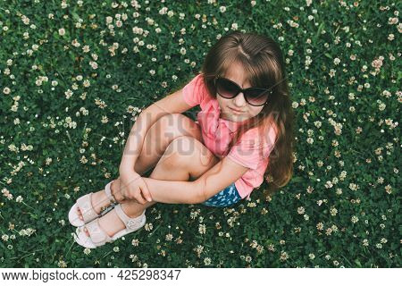 A Cute Teenage Girl Sits In The Summer On A Blooming Meadow Of Clover In Sunglasses. Holidays, Relax