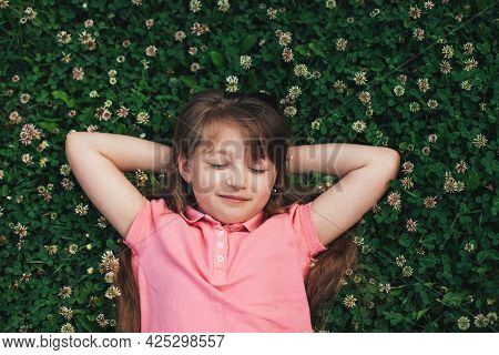 A Cute Teenage Girl Lies On A Blooming Meadow Of Clover With Her Eyes Closed. Holidays, Summer Holid