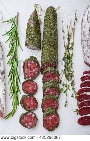 Variety Of Dry Cured Fuet And Chorizosalami Sausages, Whole And Sliced On White Textured Background,