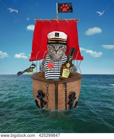 A Gray Cat Captain In A Sailor's Hat With A Bottle Of Rum Is On A Sailboat With A Red Sail On The Se