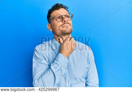 Young hispanic man wearing casual clothes and glasses touching painful neck, sore throat for flu, clod and infection