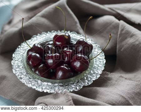 Still Life With A Glass Bowl Filled Of Sweet Cherry. Heap Of Ripe Sweet Cherry For Breakfast Or For