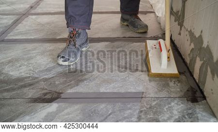 Laying Floor Tiles, Tiler Cleaning Tiles After Filling Up Joints. Cleaning Tiles After Laying On The