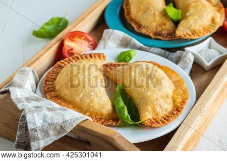 Chebureks Or Pasties, Traditional Deep-fried Meat Pies On A Wooden Tray On A Light Concrete Backgrou
