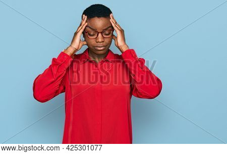 Young african american woman wearing casual clothes and glasses suffering from headache desperate and stressed because pain and migraine. hands on head.