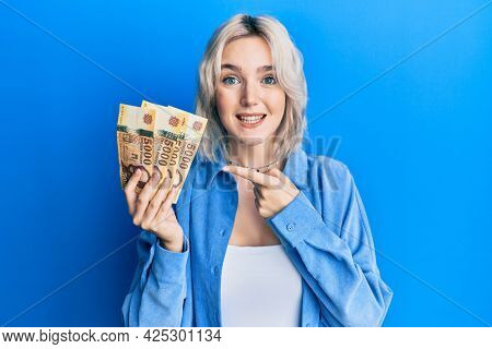 Young blonde girl holding hungarian forint banknotes smiling happy pointing with hand and finger