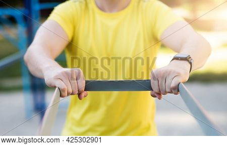 Man stretching with elastic rubber during street workout