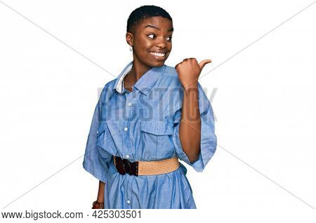 Young african american woman wearing casual clothes smiling with happy face looking and pointing to the side with thumb up.