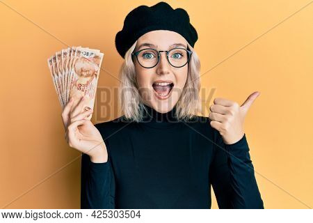 Young blonde girl holding 50 turkish lira banknotes pointing thumb up to the side smiling happy with open mouth