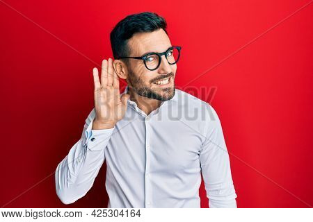 Young hispanic businessman wearing shirt and glasses smiling with hand over ear listening an hearing to rumor or gossip. deafness concept.