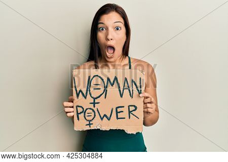 Young latin woman holding woman power banner afraid and shocked with surprise and amazed expression, fear and excited face.
