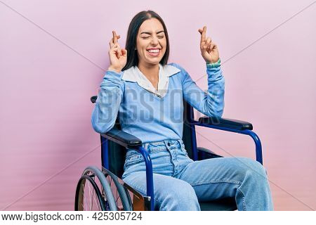 Beautiful woman with blue eyes sitting on wheelchair gesturing finger crossed smiling with hope and eyes closed. luck and superstitious concept.