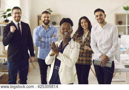 Happy Business Leader Clapping Hands Standing In Office With Team Of Her Employees