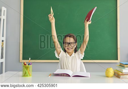 Schoolgirl At School. Funny Schoolgirl In The Eyes Raised Her Hands Up In The Classroom.
