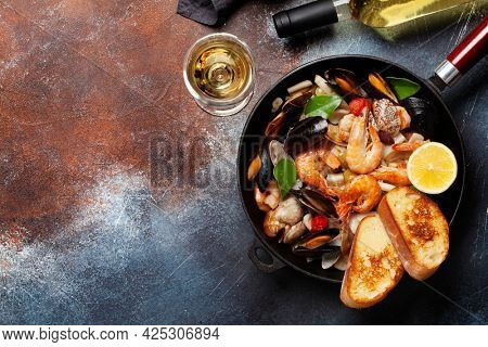 Mixed grilled seafood. Various roasted shrimps, mussels and shellfish in frying pan and white wine. Top view flat lay with copy space