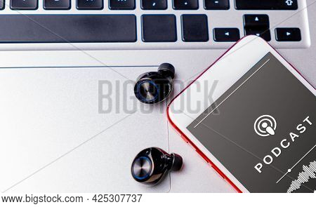 Close-up Of A Smartphone Playing A Podcast, With Earphones, On A Laptop. Podcast Audience