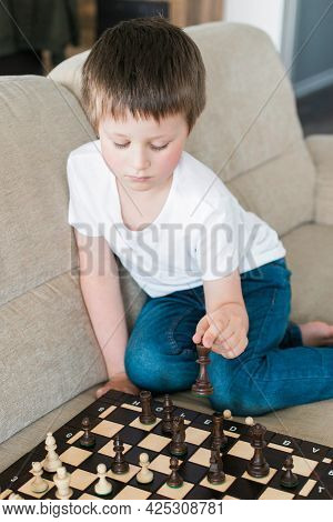 Cute Boy 6 Years Old Learns To Play Chess At Home On The Couch. Authentic Moments Of Life. Board Gam