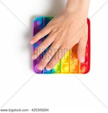 A Child Push Sensory Popit Isolated On White Background Background. Antistress Pop It Toy. Rainbow S