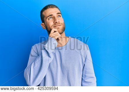 Young caucasian man wearing casual clothes thinking concentrated about doubt with finger on chin and looking up wondering