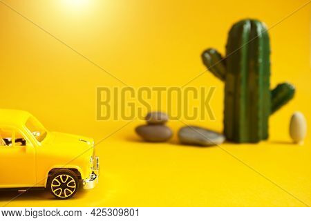 Summer Trip By Car-a Yellow Car On A Background With A Cactus-a Tour To The Desert, To The Sea. Inde