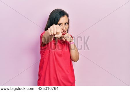 Middle age hispanic woman wearing casual clothes punching fist to fight, aggressive and angry attack, threat and violence