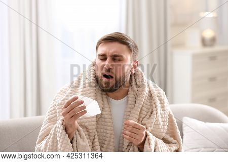 Young Man Suffering From Runny Nose In Living Room