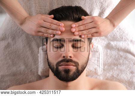 Young Man Receiving Facial Massage In Beauty Salon, Top View