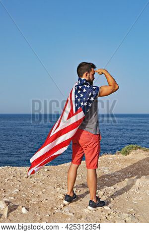 Man Poses In Form Of Hero And American Flag As Cloak Outdoor. Independence Day Of United States Of A