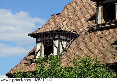 Attic Of An Old Abandoned Private House With An Empty Window Under A Brown Tiled Roof Against A Blue