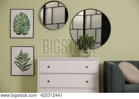 White Chest Of Drawers With Lamp And Mirrors On Wall In Living Room. Interior Design