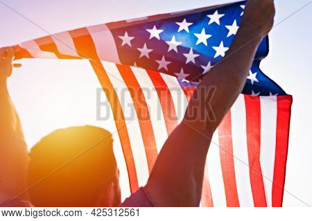 Low Angle View Of Man\'s Raised Hands With Waving American Flag Against Clear Blue Sky. Independence
