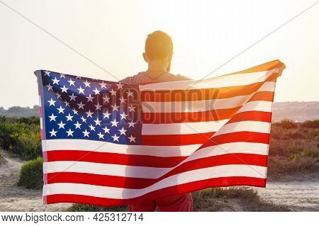 Rear View Of Man Holding Waving Usa American Flag Against Sunset Sky Outdoor. Independence Day Of Un