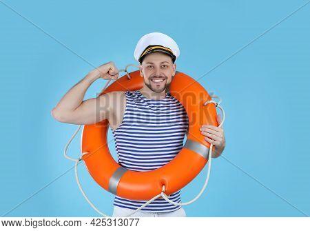 Sailor With Orange Ring Buoy Showing Biceps On Light Blue Background