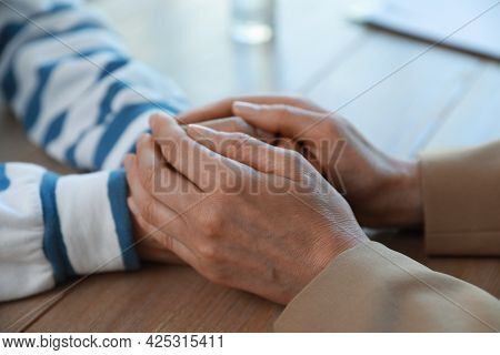Psychotherapist Holding Patient's Hands At Table Indoors, Closeup