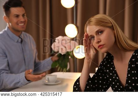 Man Giving Flowers To Displeased Young Woman In Restaurant. Failed First Date