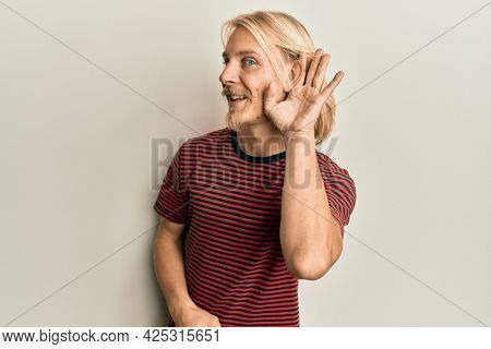 Caucasian young man with long hair wearing casual striped t shirt smiling with hand over ear listening and hearing to rumor or gossip. deafness concept.