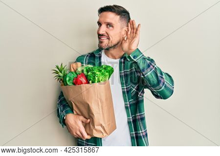 Handsome man with beard holding paper bag with groceries smiling with hand over ear listening an hearing to rumor or gossip. deafness concept.