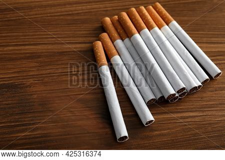 Pile Of Cigarettes On Wooden Table. Space For Text