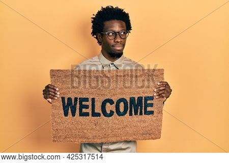 Young african american man holding welcome doormat smiling looking to the side and staring away thinking.