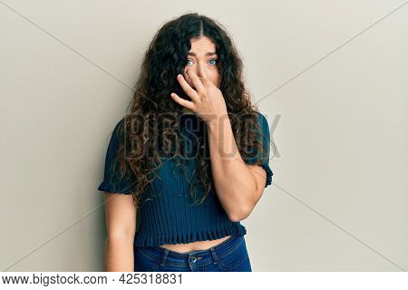 Young brunette woman with curly hair wearing casual clothes smelling something stinky and disgusting, intolerable smell, holding breath with fingers on nose. bad smell