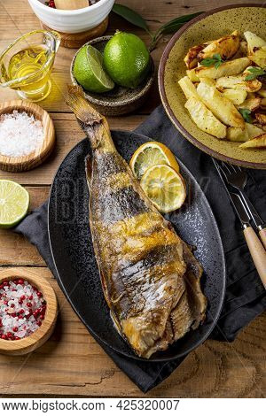 Baked Sea Bass Or Lingcod Fish With Potatoes On The Wooden Table, Vertical Photo