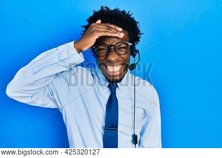 Young african american man wearing call center agent headset stressed and frustrated with hand on head, surprised and angry face