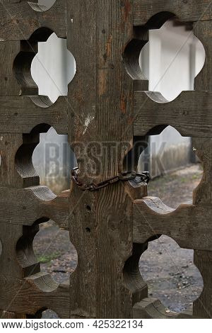 Fragment Of A Wooden Gate With Carved Holes. The Gate Is Closed With An Iron Chain.