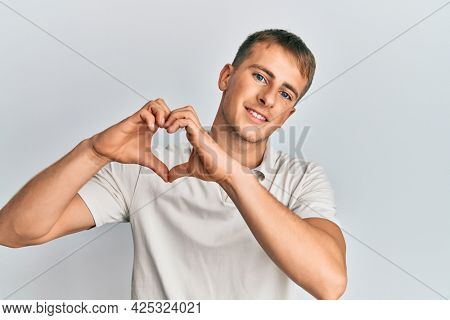 Young caucasian man wearing casual white polo smiling in love doing heart symbol shape with hands. romantic concept.