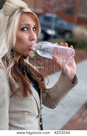 This young blonde female is drinking some bottled water. poster