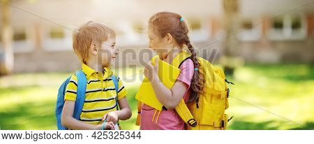 Two Cute Children Standing In The Schoolyard Park