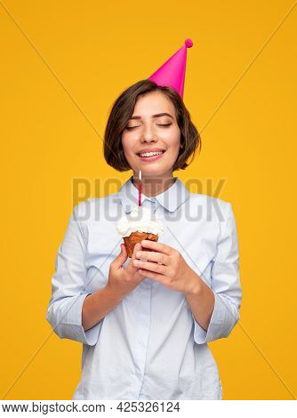 Optimistic Young Brunette In Party Hat Keeping Eyes Closed And Holding Cupcake With Candle While Mak